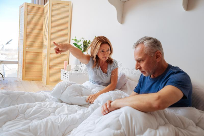 Angry wife asking her husband to go away from the bedroom stock photo