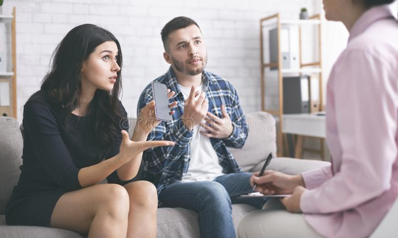 Angry wife blaming husband for cheating at marital therapy session. Angry wife showing sms from mistress to husband, blaming him for cheating in front of stock photos