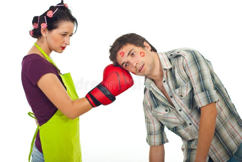 Angry wife boxing husband. Angry wife boxing unfaithful husband isolated on white background stock images