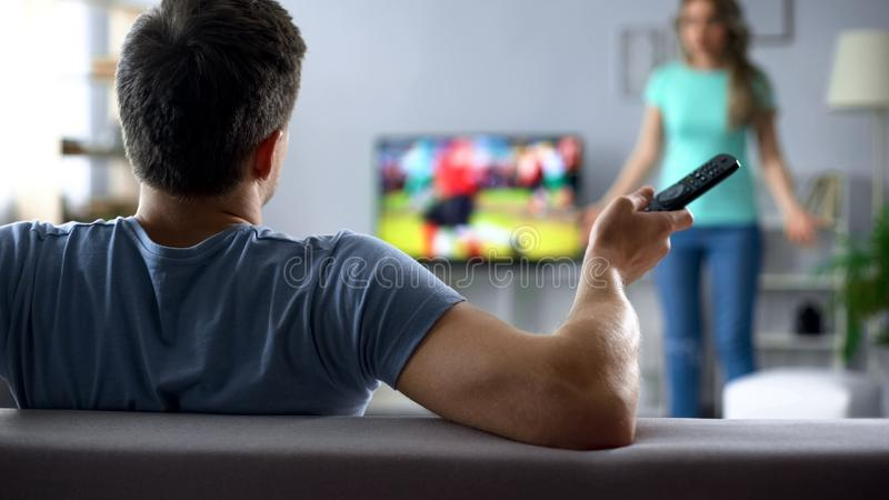 Angry wife quarreling with husband watching football game, conflict in relations. Stock photo royalty free stock photography