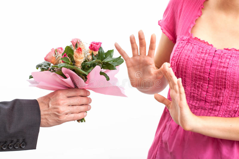Angry wife refusing apology. Angry wife refusing a flowers for apology stock photo