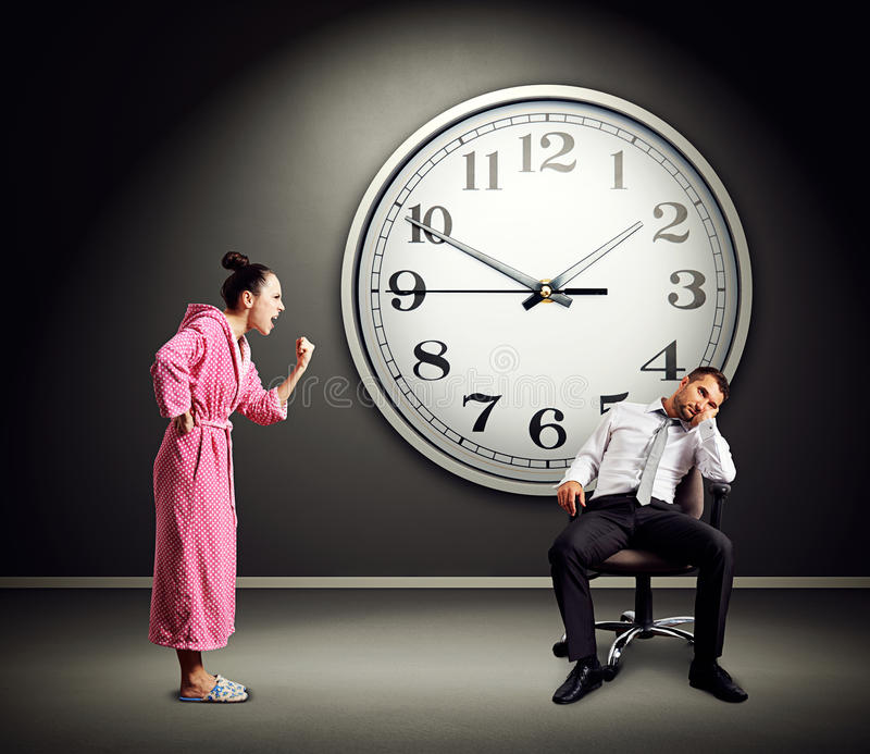 Angry wife screaming at lazy husband. Photo in dark room with big clock on the wall royalty free stock image