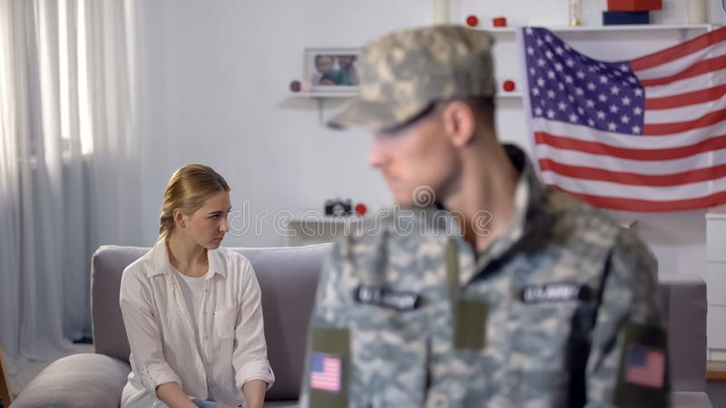 Angry wife sitting on sofa, military husband on foreground, misunderstanding. Stock photo royalty free stock photo