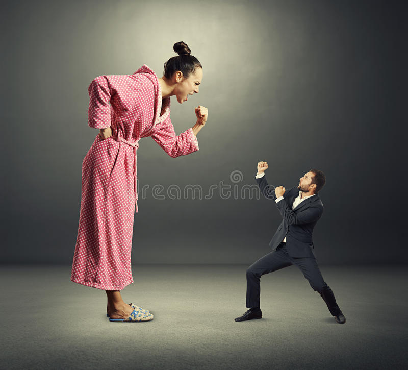 Angry wife and small henpecked husband. Quarrel between angry wife and small henpecked husband over dark background stock images