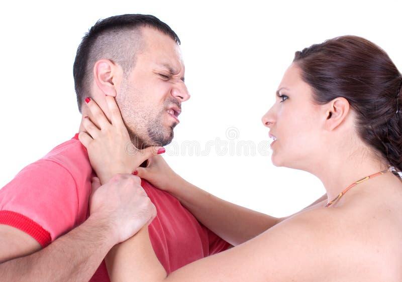 Angry wife try to strangle unfaithful husband. Angry wife from front try to strangle unfaithful husband, studio shot royalty free stock photo