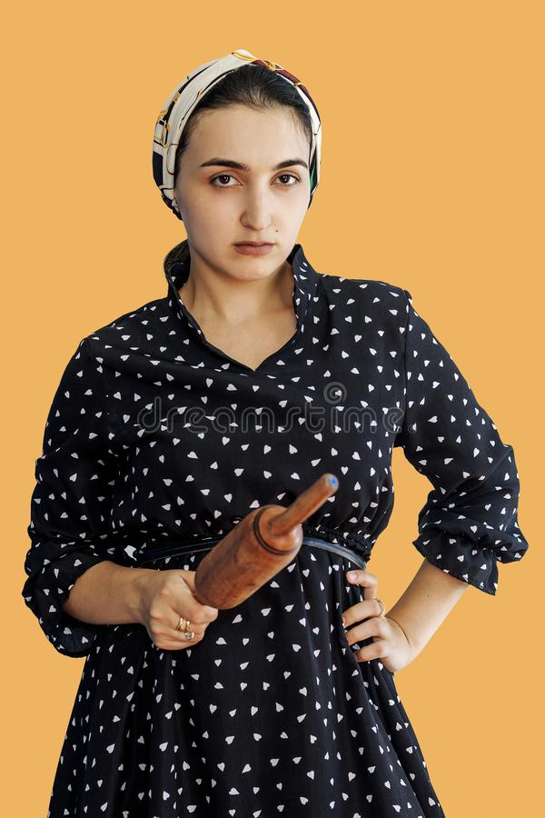 Angry wife waiting for her husband. Aggressive young middle-eastern woman holding dough rolling pin stock photos