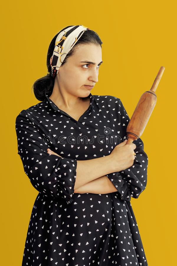 Angry wife waiting for her husband. Aggressive young middle-eastern woman holding dough rolling pin royalty free stock photography