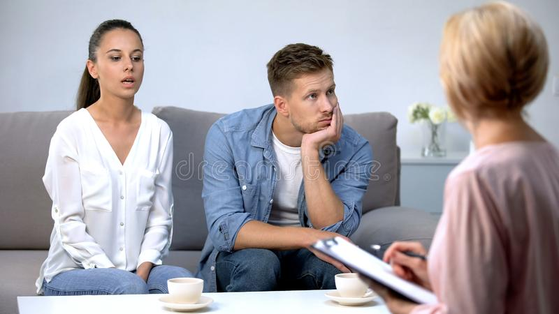 Angry woman blaming husband at psychologist consultation, risk of divorce. Angry women blaming husband at psychologist consultation, risk of divorce, stock photo royalty free stock images