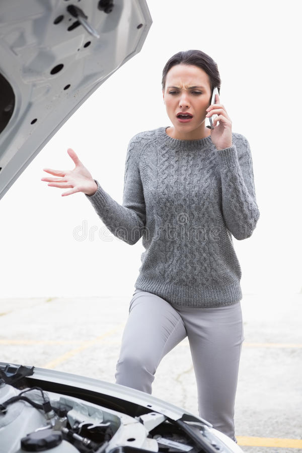 Angry woman calling for assistance after breaking down. In a car park royalty free stock photos