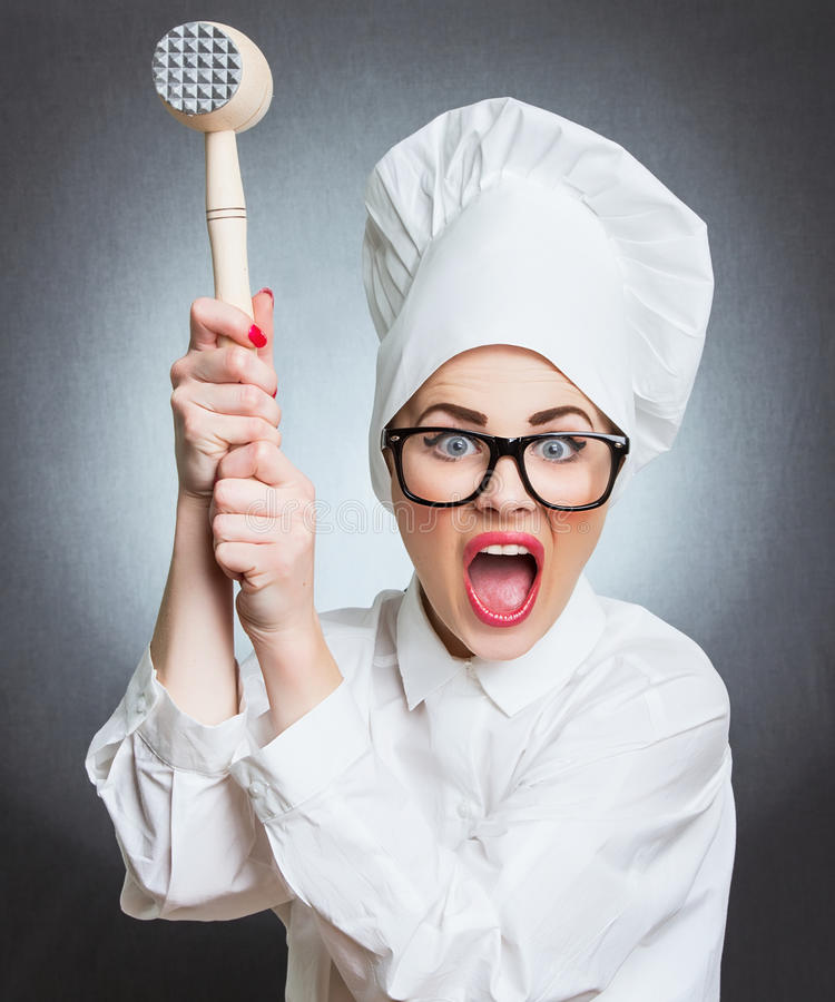 Angry woman cook - chief. Angry woman cook trying to hit with a hammer over a gray background. Funny photo stock photography