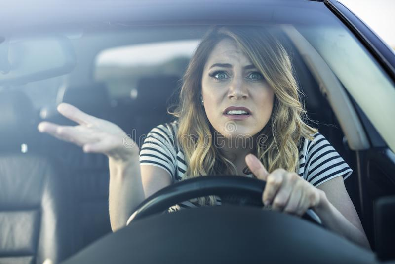 Angry woman driving a car. stock image
