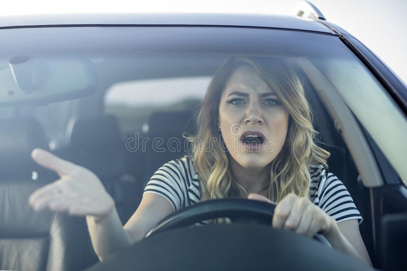 Angry woman driving a car. stock photos