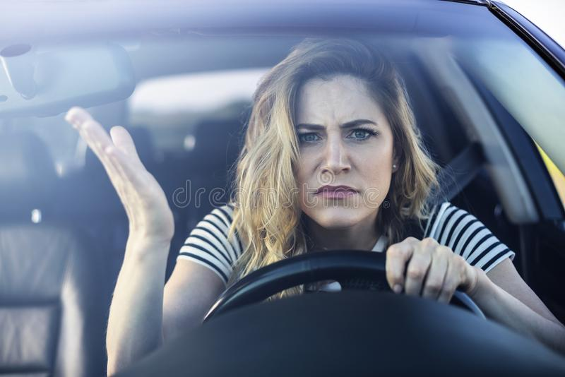 Angry woman driving a car. stock images