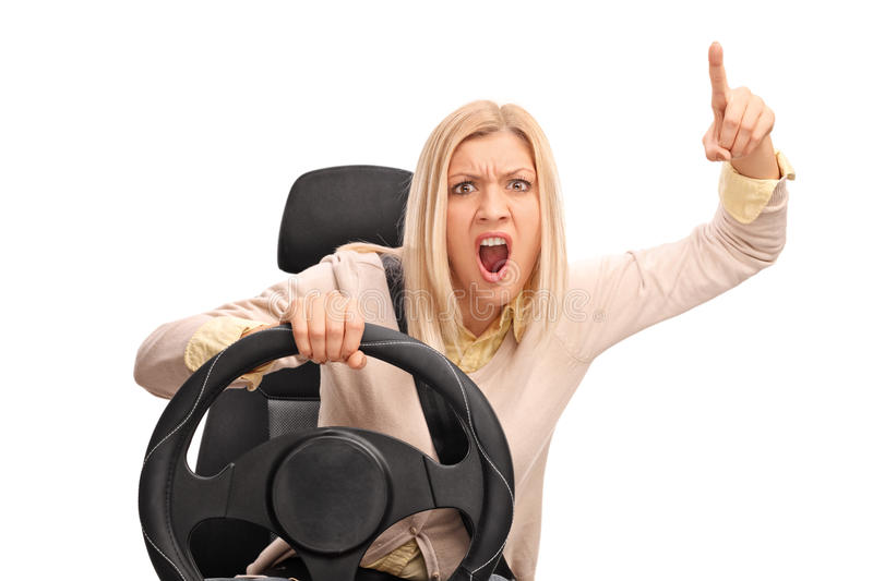Angry woman driving and shouting. Angry woman pretending to drive and shouting towards the camera isolated on white background stock photos