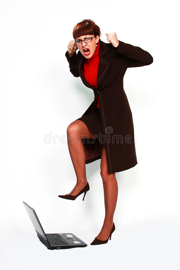 Angry woman with eyeglasses smashing computer royalty free stock images