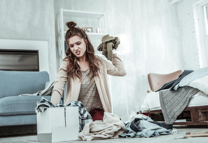 Angry woman getting rid of her husbands clothes royalty free stock photo
