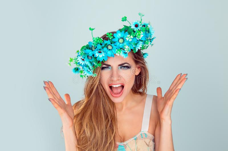 Angry woman with headband from flowers screaming in horror stock images