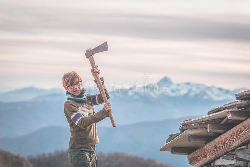 Angry woman holding an axe. Scenic background with mountain peaks, misty valley and moody sky, on the Alps. royalty free stock photo
