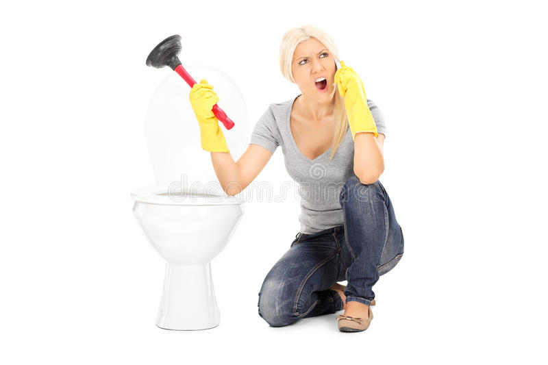 Angry woman holding plunger and talking on phone. Seated by a toilet isolated on white background royalty free stock photos