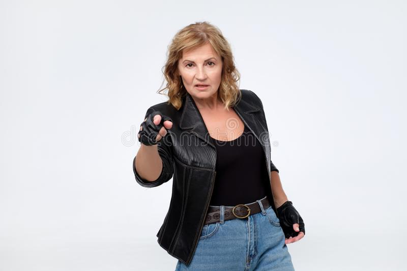 Angry woman in leather jacket pointing finger at camera stock image