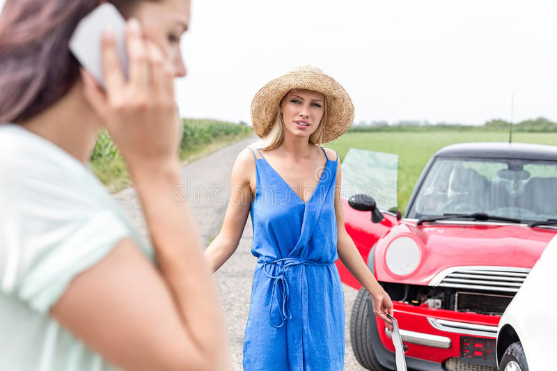 Angry woman looking at female using cell phone by damaged cars on road royalty free stock photography