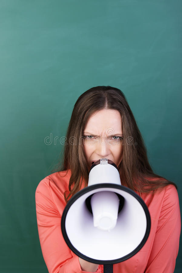 Angry woman with a megaphone. Angry young woman with a megaphone raised to her lips and a frown on her face in front of a green background with copyspace stock images