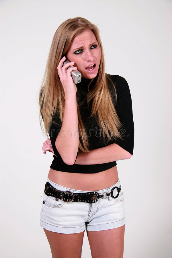Angry woman with mobile. Angry or unhappy young woman with mobile telephone; studio background stock photo