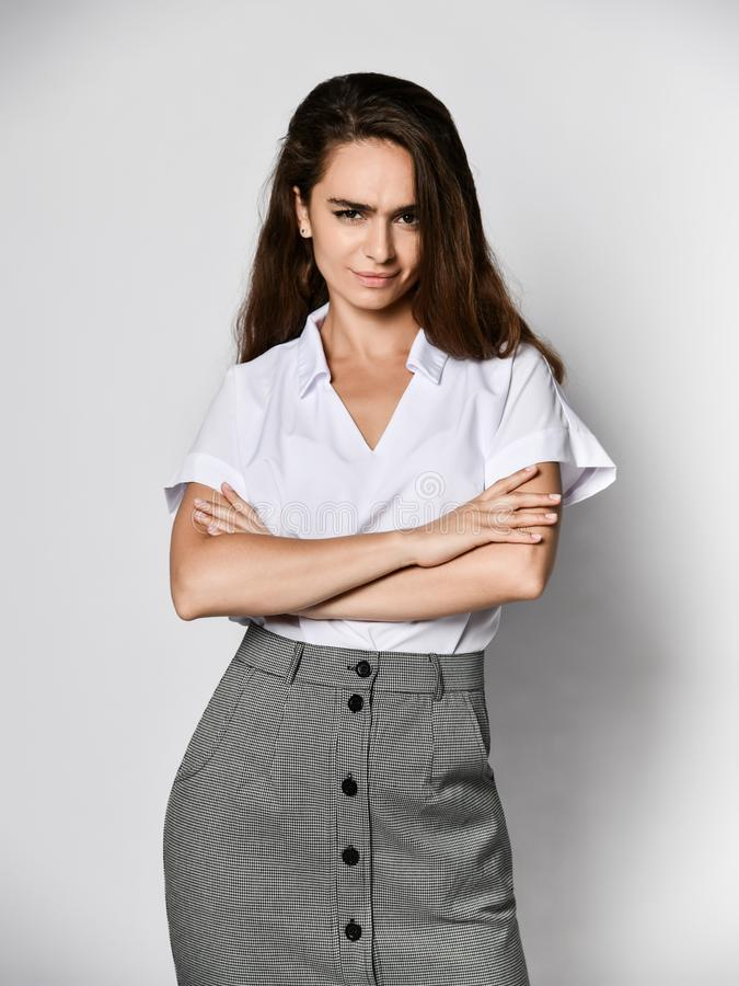 Beautiful woman office manager posing in a new casual white blouse and classic straight dark skirt. Angry woman office manager clouse her arms over her chest in royalty free stock image
