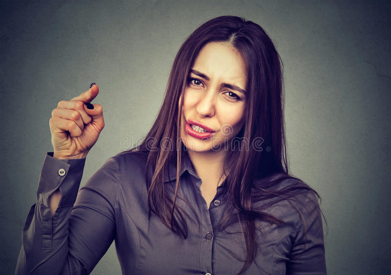 Angry woman pointing her finger accusing someone. Angry young woman pointing her finger accusing someone stock images