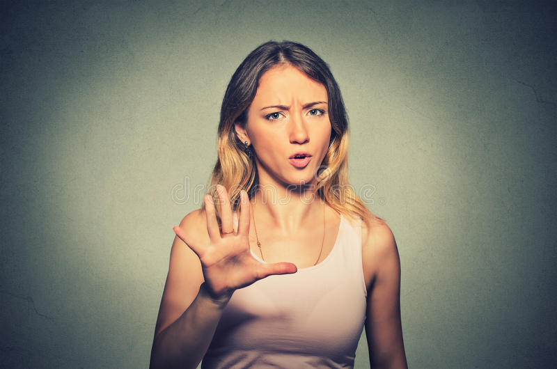 Angry woman raising hand up to say no stop. Closeup portrait of angry annoyed woman raising hand up to say no stop right there on gray background. Negative human royalty free stock image