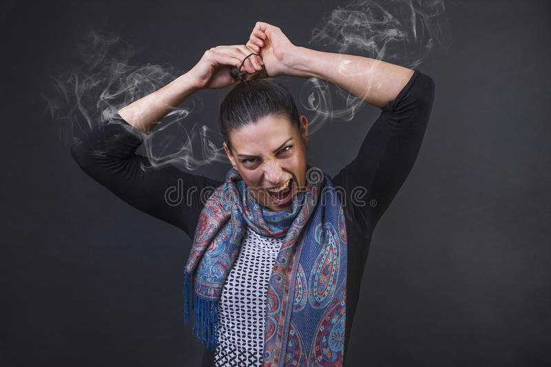 Angry woman screaming in frustration, furious unable to tie her pony tail and steaming out of her ears royalty free stock photo