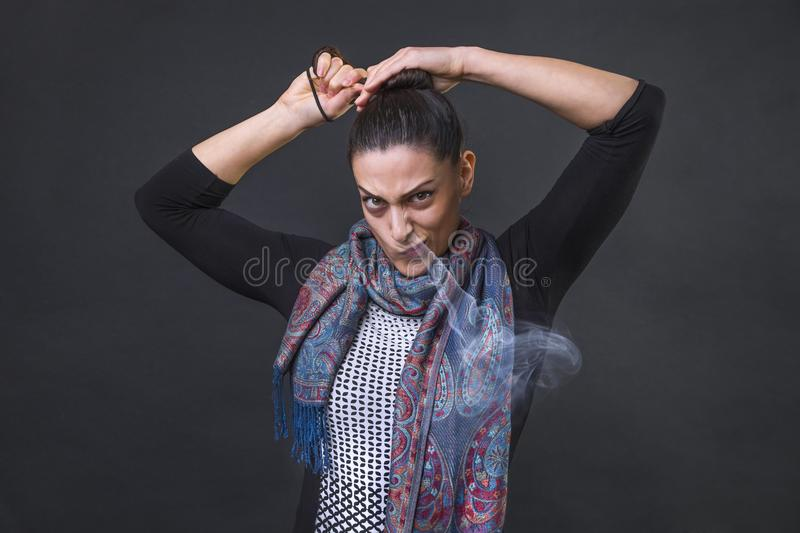 Angry woman screaming in frustration, furious unable to tie her pony tail and steaming out of her nose stock photo