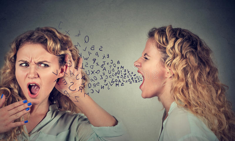 Angry woman screaming at shocked herself stock images