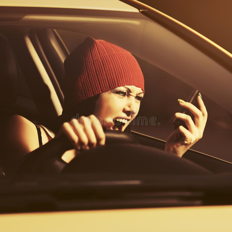 Angry woman shouting on cell phone driving a car royalty free stock photo