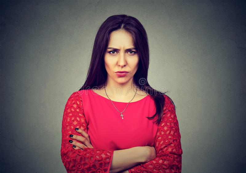 Angry woman standing with arms folded on gray background. Portrait of angry woman standing with arms folded on gray background royalty free stock images