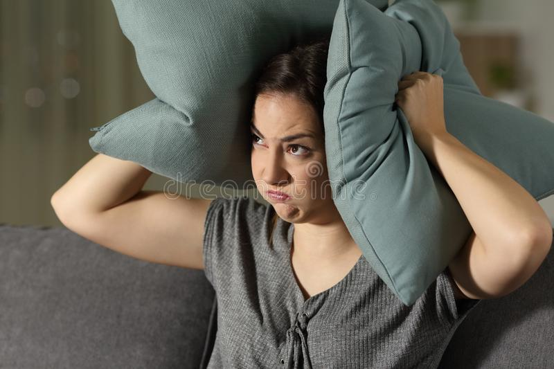 Angry woman suffering neighbour noise. Sitting on a couch in the living room at home stock images
