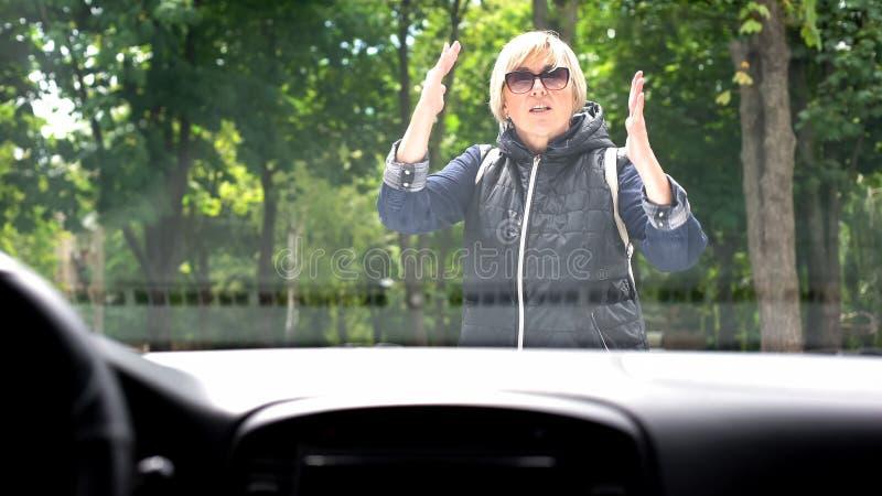 Angry woman sweater naar auto-chauffeur op parkeerplaats, wegconflict, waarschuwing stock afbeeldingen