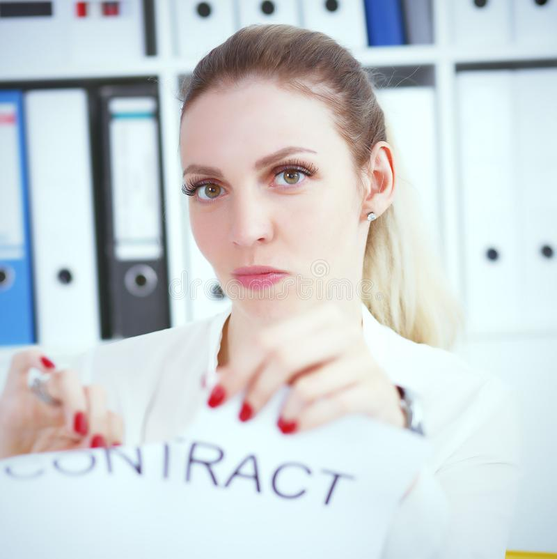 Angry woman tears agreement documents in front of camera closeup. Young woman tears agreement documents in front of camera closeup royalty free stock photo