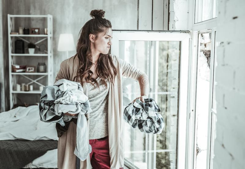 Angry woman throwing the shirts of her ex away royalty free stock images