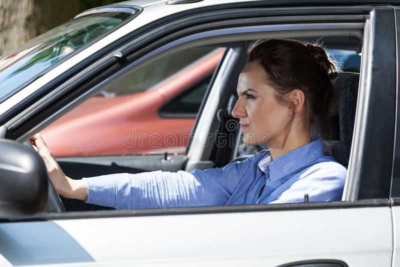Angry woman in a traffic jam. Horizontal view of angry woman in a traffic jam stock image