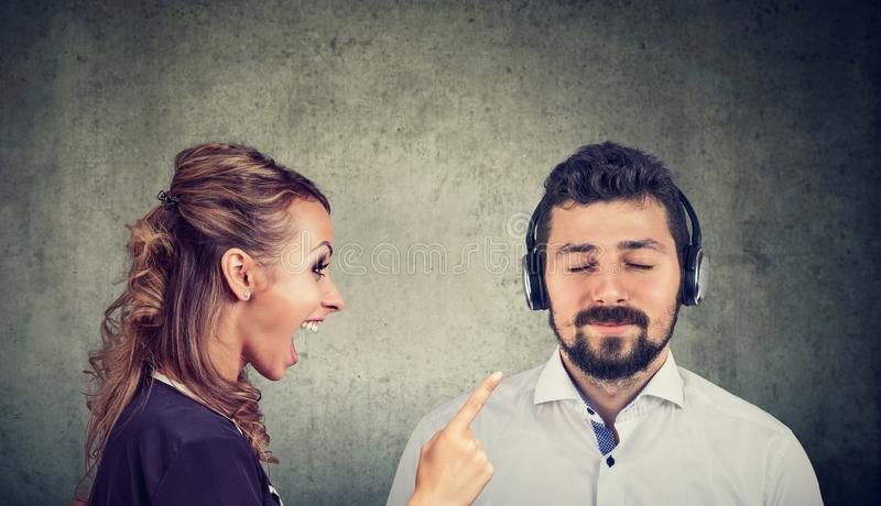 Angry woman yelling at a calm husband listening to music. Angry women yelling at a calm husband listening to music with headphones stock photo