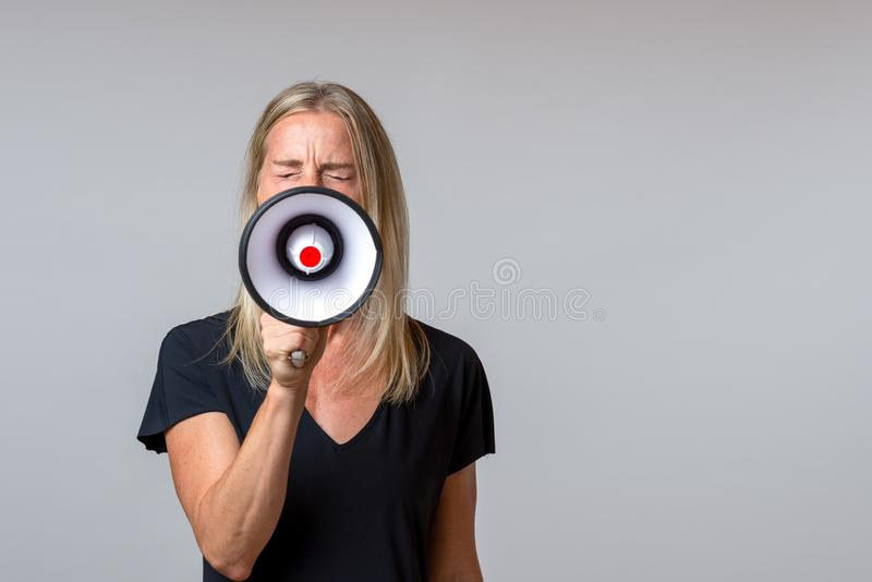 Angry woman yelling into a handheld megaphone. In a concept of activism, strike, demonstration, protest or public speaking over grey with copy space royalty free stock images