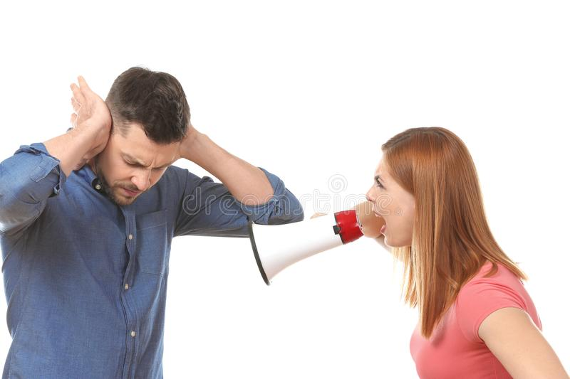 Angry woman with megaphone scolding her husband. Angry women with megaphone scolding her husband on white background stock photo