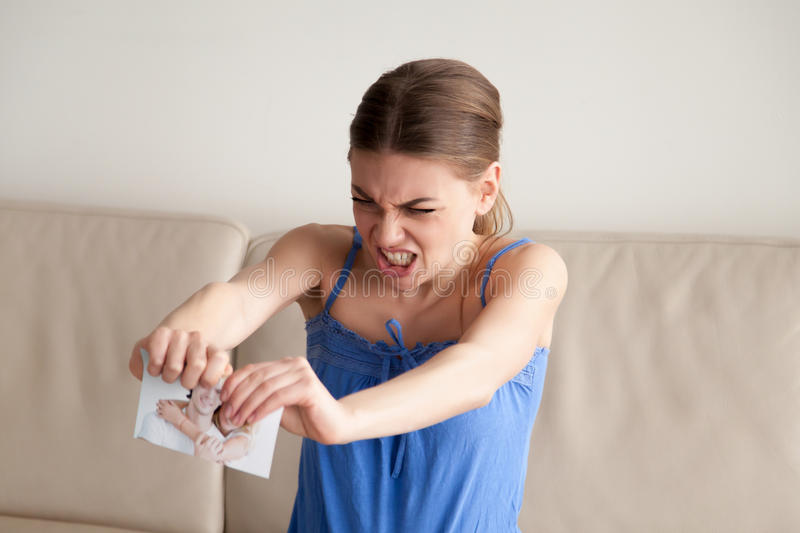 Angry woman tears paper photograph in two pieces stock image