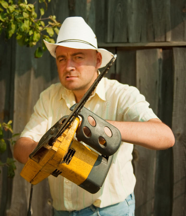 Angry worker with chainsaw. Gardener posing for the camera with his chainsaw against summer time in garden royalty free stock image