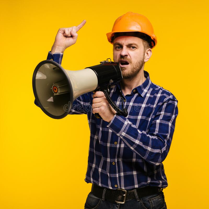 Angry worker man with a megaphone on yellow background stock photography