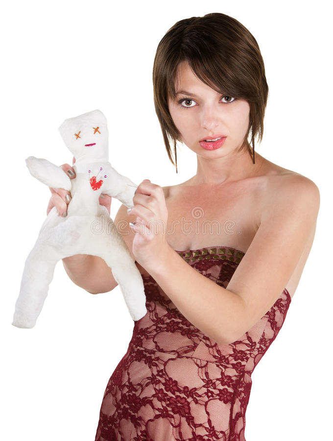 Angry Lady with Voodoo Doll. Angry young adult sticking doll with pin royalty free stock image