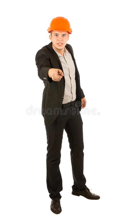 Angry young architect or engineer. Wearing an orange hardhat glaring at the camera and pointing his finger in blame, full length isolated on white royalty free stock images