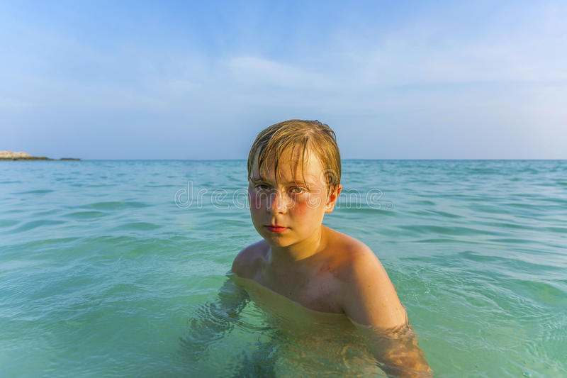 Angry young boy in the beautiful ocean stock photo