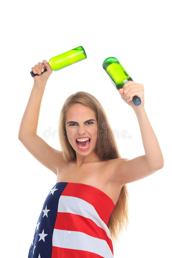 An angry girl, wrapped in a American flag, holds two bottles of alcohol and shouts aggressively. Isolated. stock image